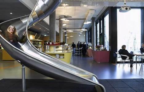 """Um escorregador conecta as zonas chamadas de """"oficinas"""" do primeiro andar com a cafeteria e um ginásio. Não é preciso esperar o elevador, é só escorregar!"""